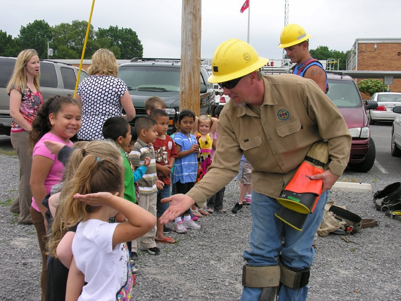 Duck River Electric technician high fiving kids