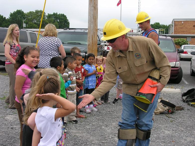 Duck River Electric technician high fiving kids