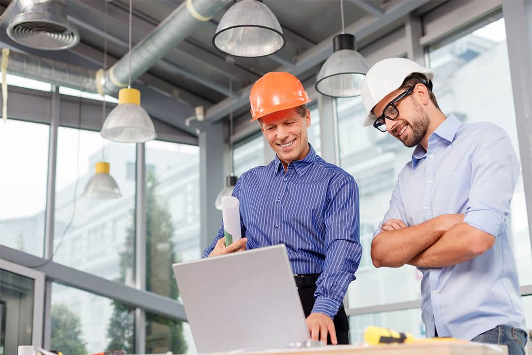 Two men in front of a laptop looks at building plans